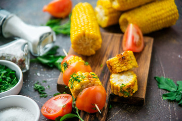 Grilled corn on skewers with tomatoes, herbs and spices on a dark background.