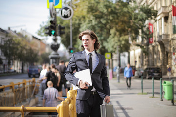 Young man in suit walking on the street.