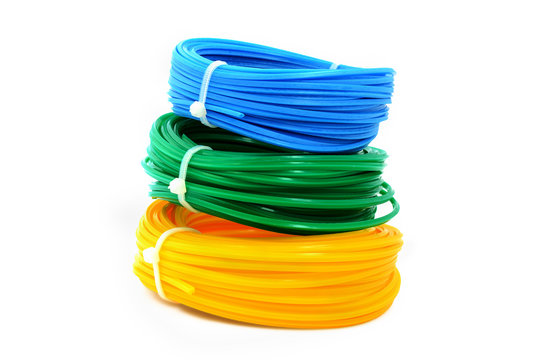 A stack of colored spools with a fishing line for the trimmer. Linear coil is yellow, blue, green for trimmer.