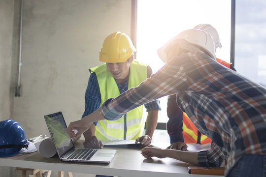 engineer team planning and discussing about construction building on table in working site