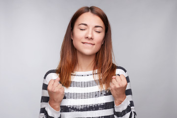 Successful pretty young lady closes eyes from happiness, keeps raised fists, dressed casually, celebrates her victory with triumph, isolated over gray studio wall. People, joy, body language concept.
