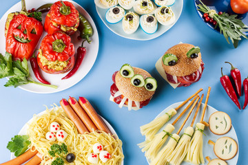 Halloween party food. Stuffed peppers with scary faces, cheese witches brooms, monster hamburgers, witch finger treats.