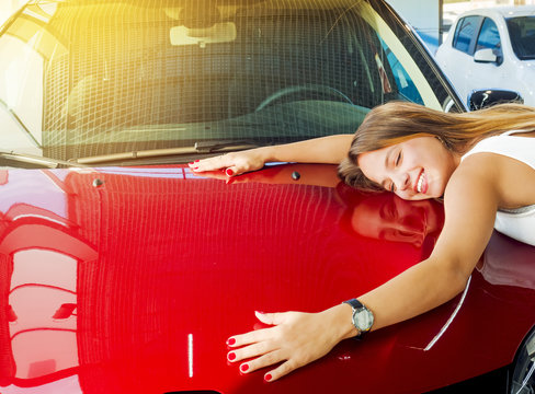 Dream about car. Gorgeous smiling woman hugging lies on the hood of new red car in the dealership.