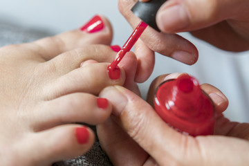 Foto auf Acrylglas Pediküre The master covers the customer's nails with varnish. Hands in gloves cares about a woman's foot nails. Pedicure, manicure beauty salon concept. Nail varnishing in red color.