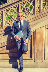 Confident European Professional travels, works in New York. Wearing gray suit, tie, leather shoes, sunglasses, holding laptop computer, Mixed Race French guy with shaved head stands on vintage street