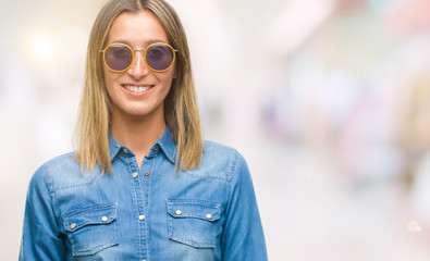 Young beautiful woman wearing sunglasses over isolated background with a happy and cool smile on face. Lucky person.