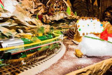 Christmas decorations against blurred background. Toy train on a track with ginger house background.