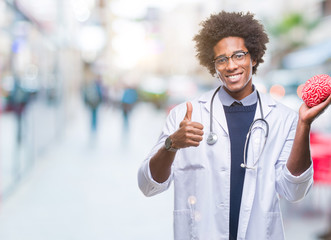 Afro american neurologist doctor or psychology man over isolated background happy with big smile doing ok sign, thumb up with fingers, excellent sign