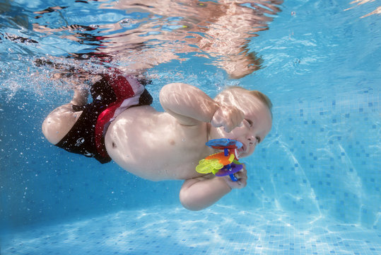 A little boy with a toy dives underwater in the pool