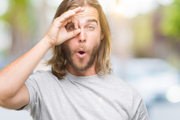 Young handsome man with long hair over isolated background doing ok gesture shocked with surprised face, eye looking through fingers. Unbelieving expression.