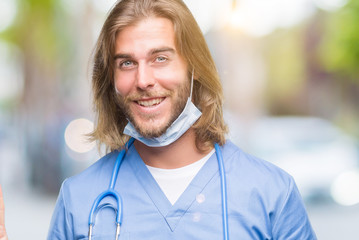 Young handsome doctor man with long hair over isolated background smiling with happy face winking at the camera doing victory sign. Number two.