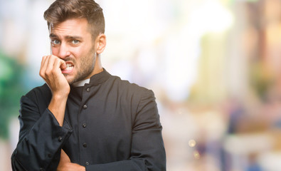 Young catholic christian priest man over isolated background looking stressed and nervous with hands on mouth biting nails. Anxiety problem.
