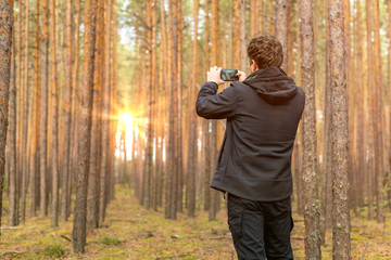 Tourist traveler taking pictures of sunrise in forest.