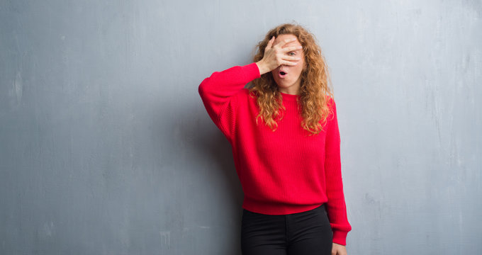 Young redhead woman over grey grunge wall wearing red sweater peeking in shock covering face and eyes with hand, looking through fingers with embarrassed expression.