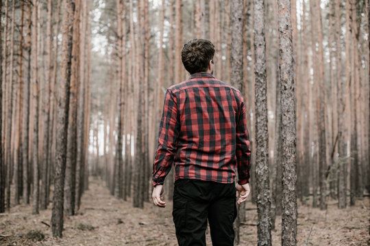Man in red plaid shirt and black military pants lost in the pine forest. Copy space. Toned