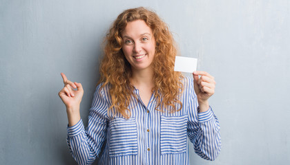 Young redhead woman over grey grunge wall holding blank visit card very happy pointing with hand and finger to the side