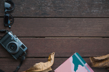 Autumn composition and accessories. Autumn leaves, retro camera, notebook. Flat lay, top view.