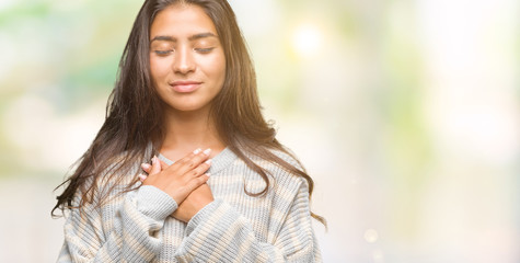 Young beautiful arab woman wearing winter sweater over isolated background smiling with hands on chest with closed eyes and grateful gesture on face. Health concept.