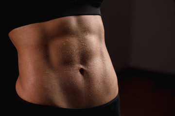 Close up of fit female abs isolated on black background with copy space. Fitness female and trained stomach, Perfect Slim Body. Sport, Bodybuilding, Fitness Concept
