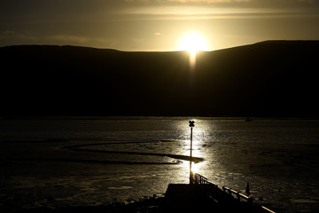 A channel in Carlingford Lough is seen in Northern Ireland while the sun sets behind hills in Ireland marking the exact border point between the Republic of Ireland and Ireland in the border town of Warrenpoint