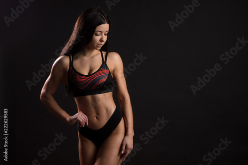 5a5a62387ea8d Sporty girl with ripped abdominal muscles in black sportswear. Tanned young  sexy athletic girl. Athlete female demonstrates chiseled biceps.