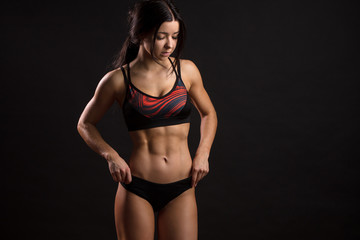 Sporty girl with ripped abdominal muscles in black sportswear. Tanned young sexy athletic fitness instructor isolated over black background with copyspace.