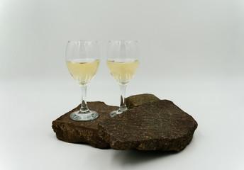 Dekorative Weißweingläser die auf Steinen stehen.