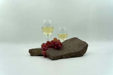 Gläser mit Weißwein, dekorativ mit roten Weintrauben auf Steinen.