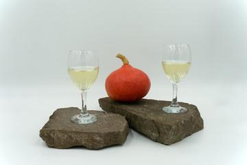 Gläser mit Weißwein, dekorativ mit Kürbis auf Steinen.