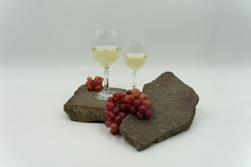Weißweingläser, dekorativ mit roten Weintrauben auf Steinen.