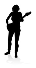 A female guitarist musician in detailed silhouette playing her guitar musical instrument.