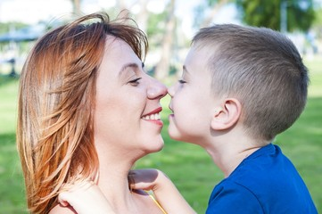 Young and beautiful Caucasian woman and her son touching each other nose to nose, face to face close up portrait, mother child love family concept. Look at each other. Single mother.