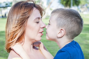 Young and beautiful Caucasian woman looking at her son, face to face close up portrait, mother child love family concept. Look at each other. Single mother.