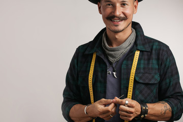 Smiling positive professional craftsman in stylish hat and small barb looking at camera standing with measuring tape on his neck over studio white background