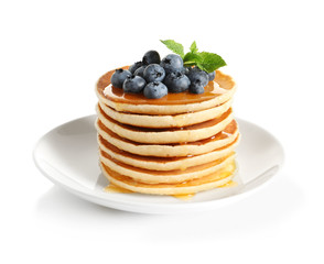 Plate with pancakes and berries on white background