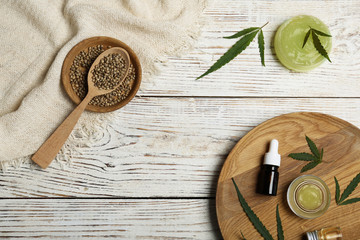 Flat lay composition with hemp lotion on wooden background