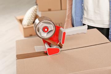 Moving box and adhesive tape dispenser indoors, closeup