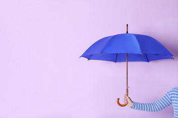 Wall Mural - Person holding bright open umbrella on color background with space for design