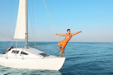 Young man relaxing on yacht during sea trip