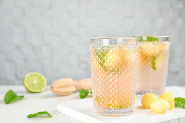 Glasses with tasty melon ball drink on table. Space for text