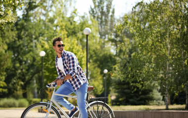 Handsome young hipster man riding bicycle in park