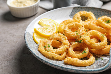 Plate with homemade crunchy fried onion rings and lemon slices on table, closeup