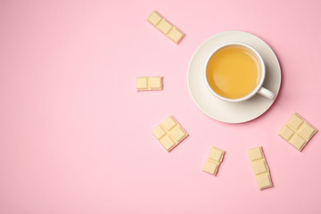 Flat lay composition with cup of tea and white chocolate on color background. Space for text