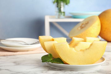 Plate with fresh delicious melon slices on table