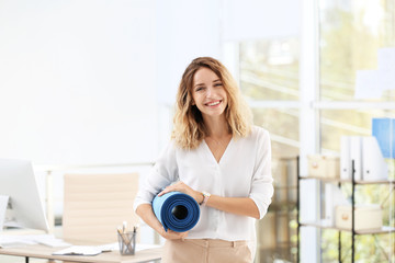 Young beautiful businesswoman holding yoga mat in office. Gym after work