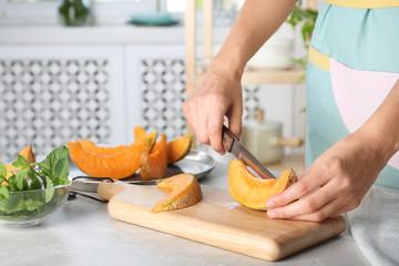 Woman slicing fresh ripe melon on light table