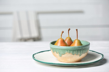 Dishware with pears on table against blurred background. Space for text