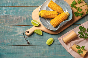 Flat lay composition with corn cobs on wooden background with space for text