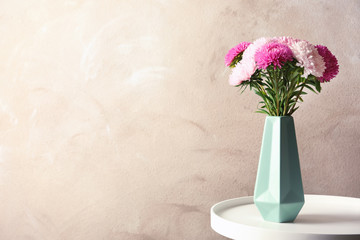 Vase with beautiful aster flower bouquet on table against color background. Space for text