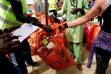 Volunteers from Zero Waste association weigh the waste picked up from a beach during the World Cleanup Day in Dakar